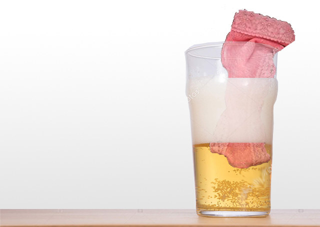 A half full glass of beer with pink undies in it.