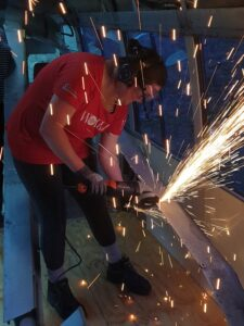 Charlotte using an angle grinder, sparks flying everywhere